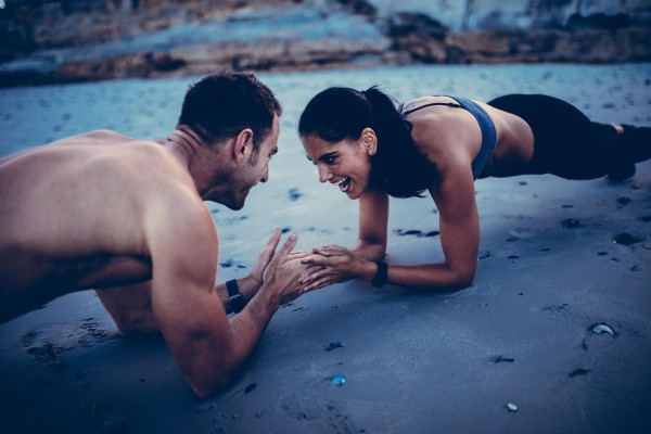 Man and woman exercising on the beach together.