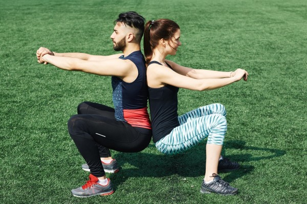 Man and woman squatting back to back.