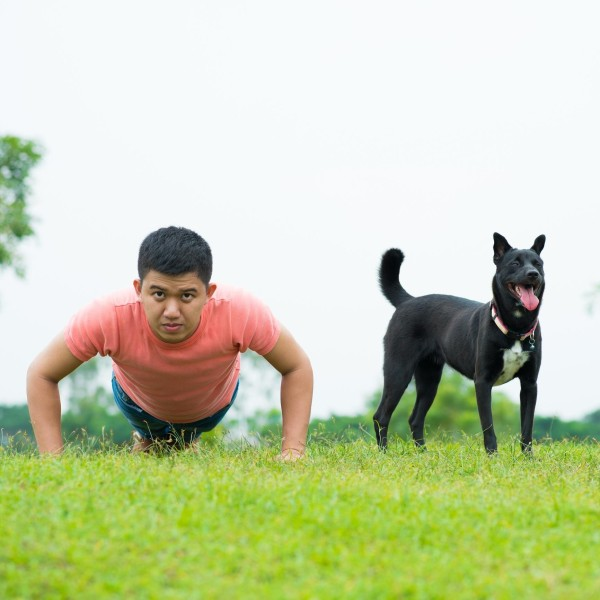 Man doing pushups with dog.