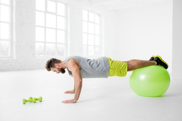 Man working out with an exercise ball.