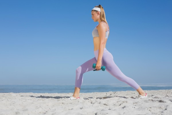 woman with dumbbells working out at the beach.
